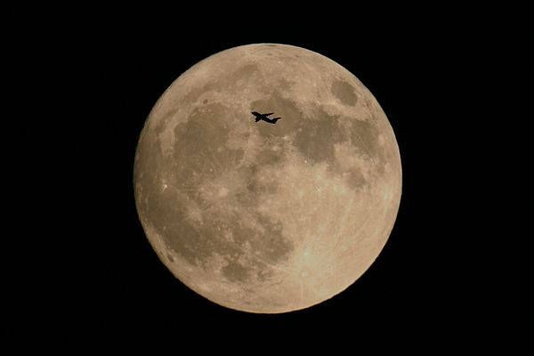 This plane flew near the horizon in front of full moon
